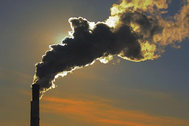 Silhouette of smoke stacks smoking up to the sky at sunset (iStock Photo)
