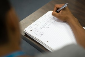 Taking notes the old-fashioned way: a high school student works on problem solving during a course on topology in the Mentor Connection program. (Peter Morenus/UConn Photo)