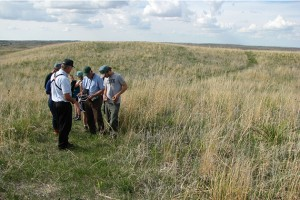 Mark Lindvall (left) of the Valentine National Wildlife Refuge identified prairie plants during a walk at the refuge. The refuge leases grassland to the Rocking Arrow Ranch in Nebraska for their cattle to graze. (Photo courtesy of Tom Morris)