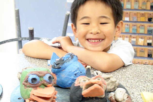 A child enjoys looking at a collection of hand-painted clay monster heads at the Community School of the Arts. (Photo courtesy of CSA)