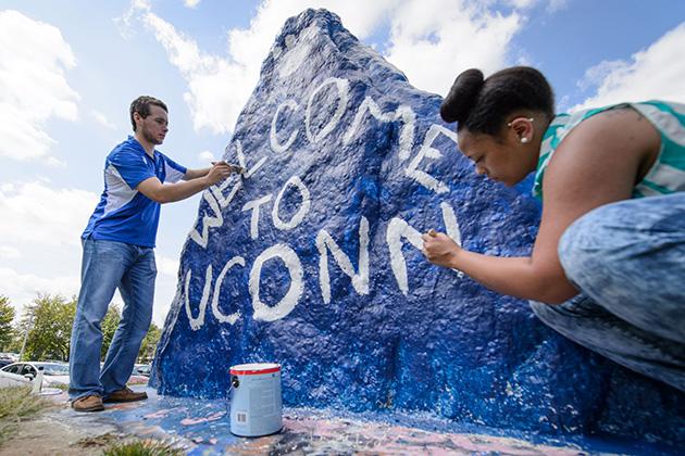 Drew Vandemore '15 (CAHNR), left, and Jasmine Kirkland '16 (CAHNR) paint 'Welcome to UConn' on the rock near the UConn Foundation Building on Aug. 20, 2014. (Peter Morenus/UConn Photo)