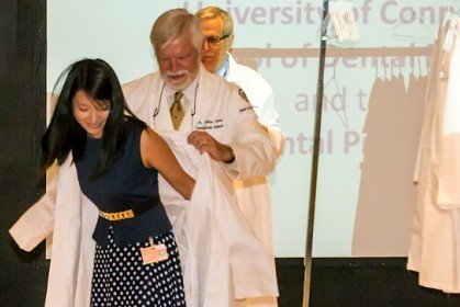 Xiaoxiao Hong, an incoming dental student, is helped into her white coat by Dr. Arthur Hand, professor of craniofacial sciences and cell biology. (Carolyn Pennington/UConn Health Photo)