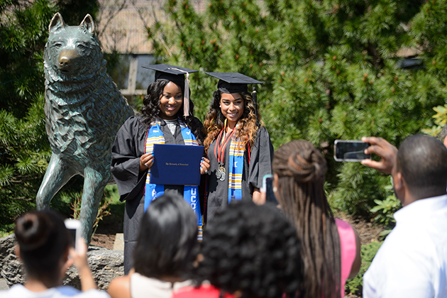 Khortney Hundley of Hamden, left, and Begum Abadin of New Britain pose for a photo with the statue of Jonathan the husky outside Gampel Pavilion following their Commencement ceremonies on May 10, 2015. (Peter Morenus/UConn Photo)