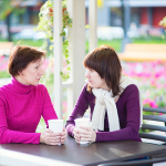 Mother and adult daughter chat over a cup of coffee. (iStock Photo)