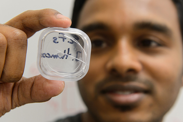 Sahan Handunkanda, a graduate student in physics and first author on the paper published by the American Physical Society, holds up a crystal of scandium trifluoride. (Peter Morenus/UConn Photo)