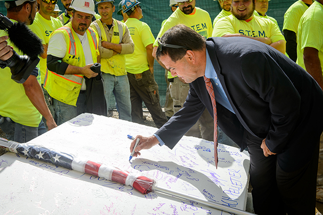 David Ouimette, executive director of first year programs & learning communities signs a concrete panel that will be hoisted to the roof during the topping off ceremony for the STEM residence hall on Sept. 14, 2015. (Peter Morenus/UConn Photo)