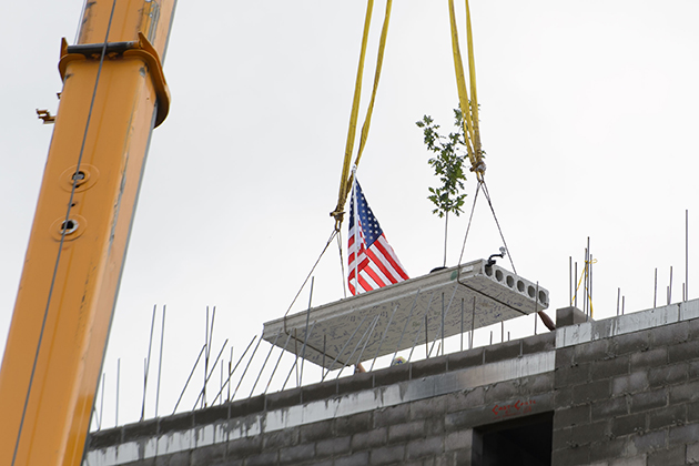 A flag and oak tree are lifted to the roof during topping off ceremony for the STEM residence hall on Sept. 14, 2015. (Peter Morenus/UConn Photo)