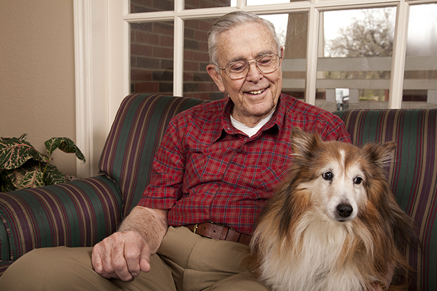 An elderly man at home with his dog. (iStockPhoto)