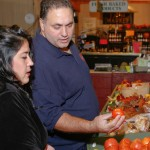 An overweight couple buying tomatoes in a grocery store. (UConn Rudd Center for Food Policy & Obesity Photo)