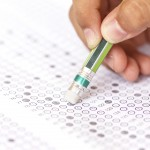 Close-up of hand with a pencil on an answer sheet. (iStock Photo)