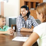 Father and son being interviewed by a professional. (iStock image)