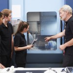 Three apprentices working with engineer on CNC machinery. (iStock Photo)