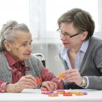 Elderly woman with caregiver figuring out a jigsaw puzzle at nursing home. (iStock Photo)