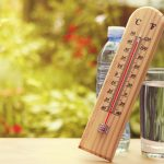 Thermometer on summer day showing high temperature over 100 degrees F, and glass of water. (iStock Photo)