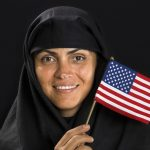 Muslim woman waving an American flag. (iStock Photo)
