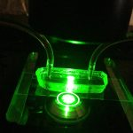Researchers in engineering professor Anson Ma's Complex Fluids Lab used a fluorescence microscope to illuminate a microfluidic device that simulates a blood vessel. The research team was then able to observe and measure how particles of different sizes behave in the bloodstream. (Anson Ma/UConn Photo)