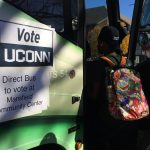A student boards a bus headed to the polling station at the Mansfield Community Center on Nov. 8, 2016. (Peter Morenus/UConn Photo)