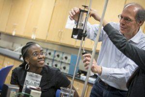 A physics professor helping students whit a physics experiment on Dec. 1, 2016. (Sean Flynn/UConn Photo)