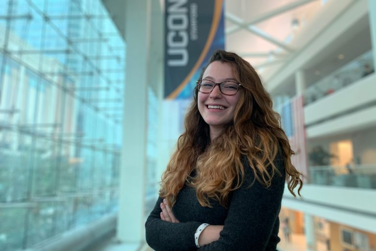Caucasian female student smiles in front of UConn sign.