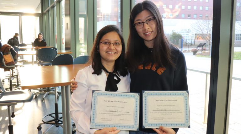 Two UConn Pharmacy students display their first and second place certificates from the 2019 AAPS Rearearch Symposium at URI