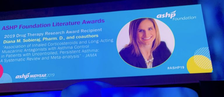 Announcement and photo on big screen at ASHP midyear event featuring Diana Sobieraj who received the 2019 ASHP Foundation Literature Award