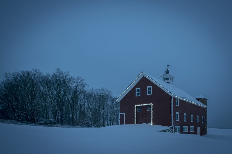 The Red Barn on Horsebarn Hill lit up for the holidays during a snowstorm.