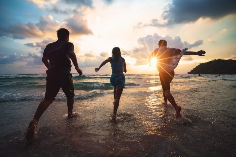 Three people running on a beach at sunset illustrate the idea of happiness.