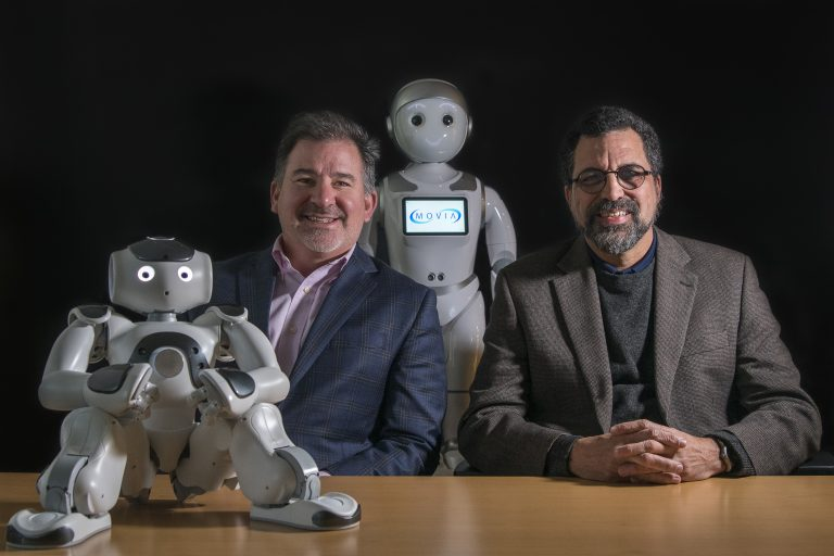 two businessmen sitting with two robots