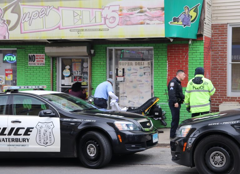 Waterbury police officers gather around a stretcher on a city street after an opioid overdose.