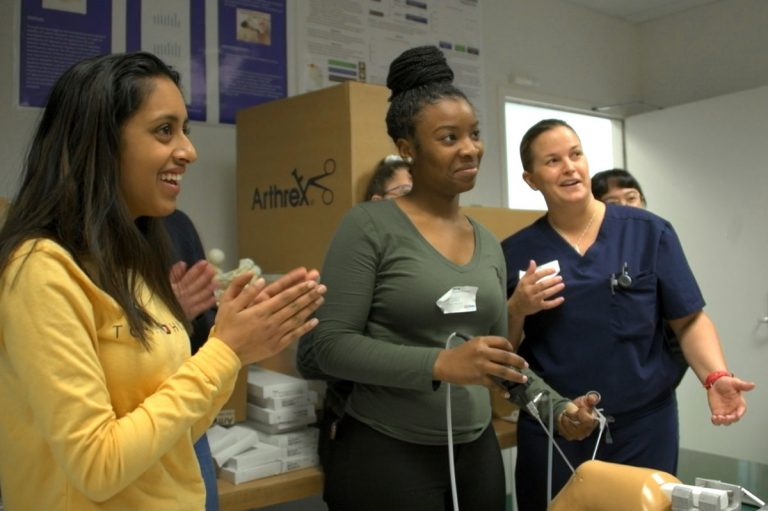 High school student peforming mock arthoscopic surgery, cheered on by another student and Dr. Katherine Coyner