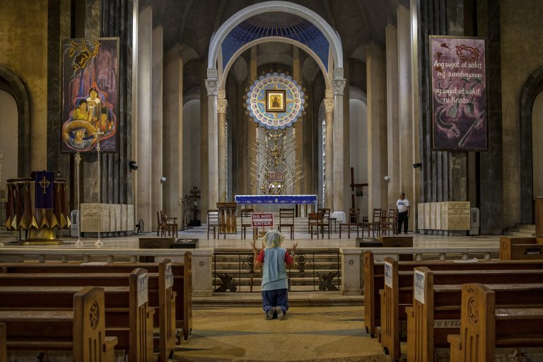 A woman kneels in prayer in an empty Catholic cathedral in the Philippines.