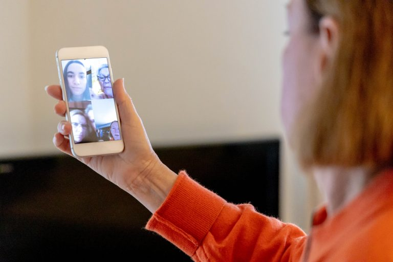An older woman has a video chat on her phone with a younger woman.