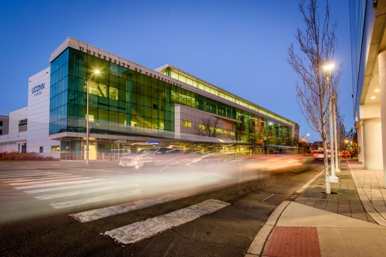 A picture of UConn Stamford at night, with cars driving by, leaving streaks of light behind them.