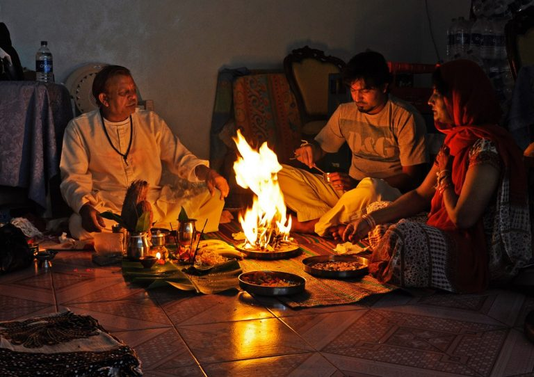 A family gathers around a traditional meal, with an open flame in the middle of the meal.
