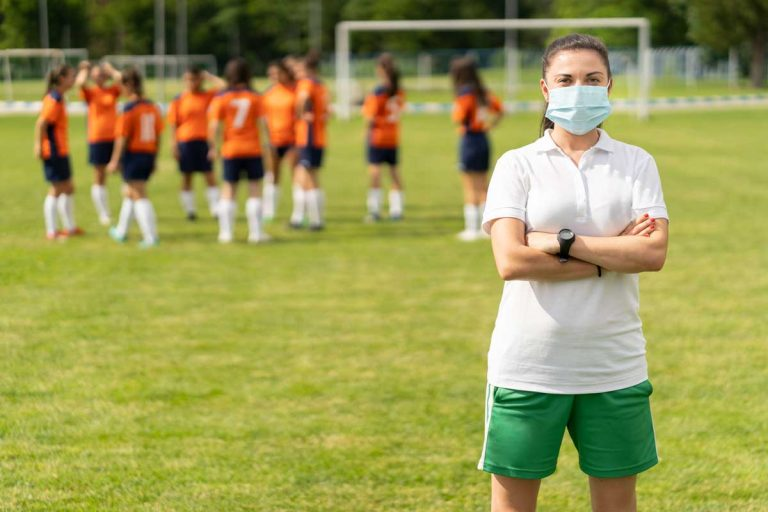 Young female soccer coach wearing surgical mask