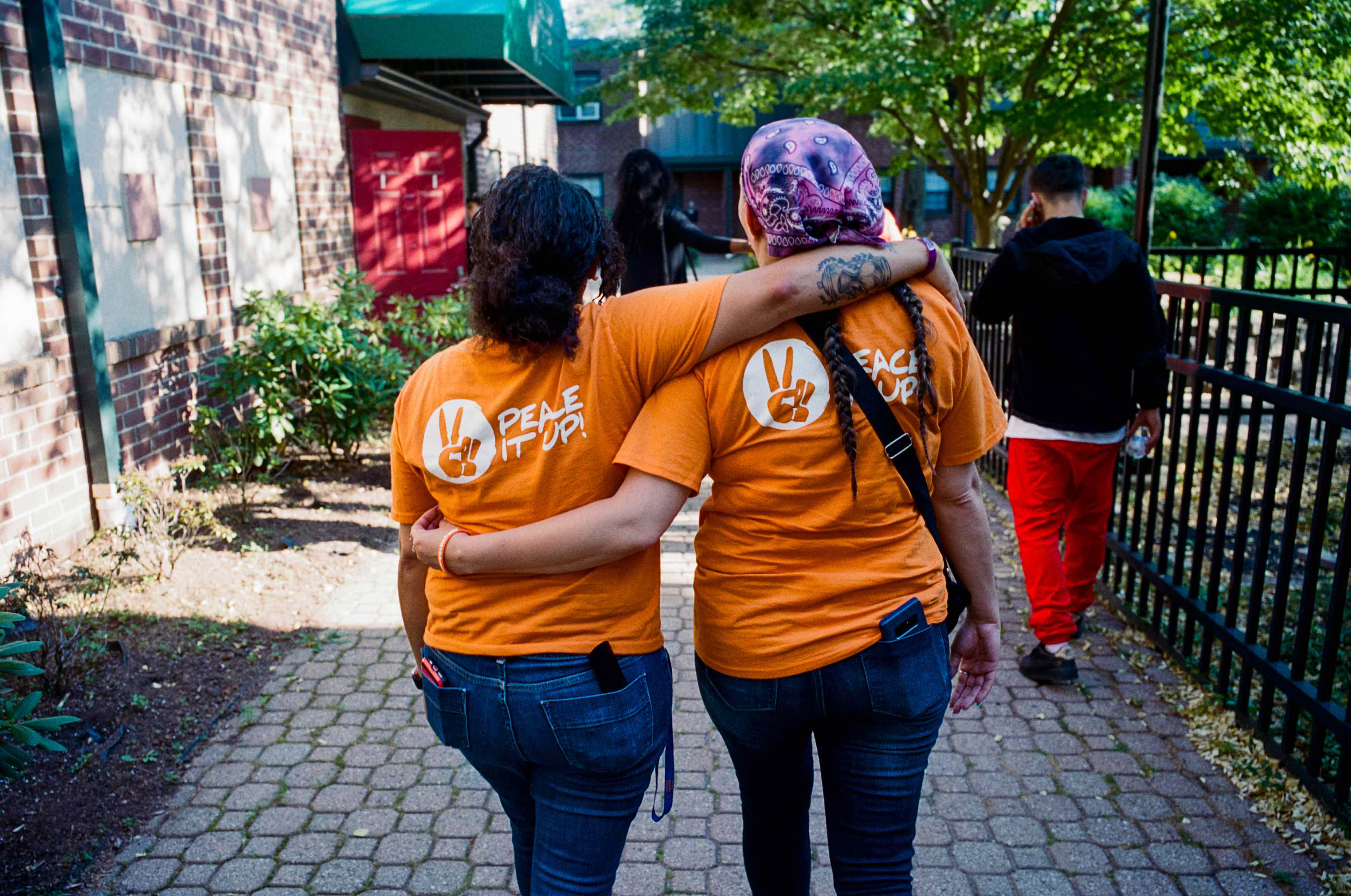 Two women with their backs to the camera embracing
