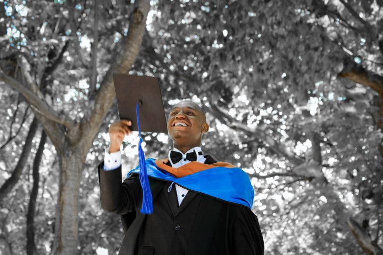 Black teenager smiling in cap and gown