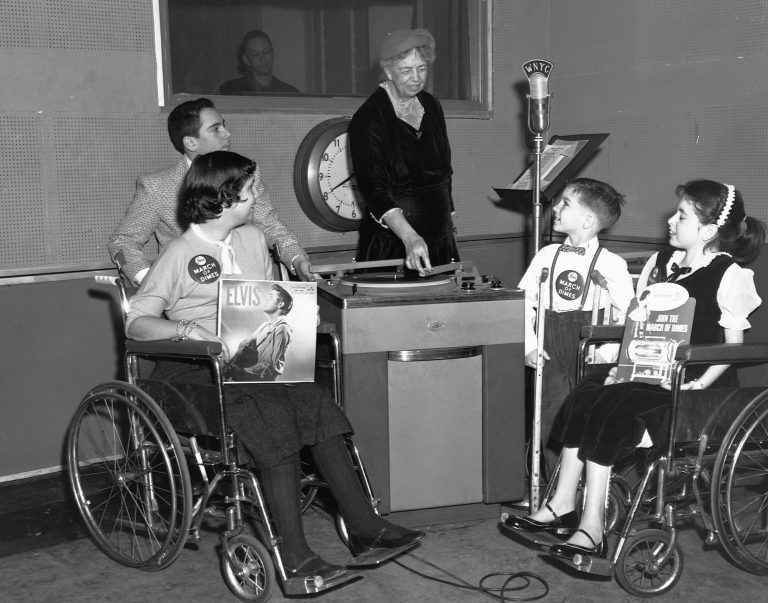 Eleanor Roosevelt acts as a disk jockey for children afflicted with polio. The purpose of the broadcast was to generate interest in a series of talent shows nationwide benefiting the March of Dimes. The children in the studio with Mrs. Roosevelt are (left to right): Florence Krieger, 15; Allen Fox, 13; George Redmond, 9; and Joyce Alexander, 12.