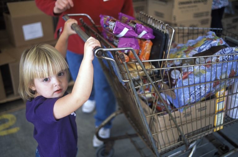 A small child pushes a shopping cart full of groceries at a food pantry.