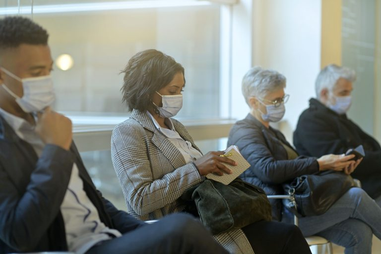 Patients sitting in waiting room with face masks during the COVID-19 pandemic. Even as vaccination rates rise, new variants of the coronavirus are prompting concern among experts.