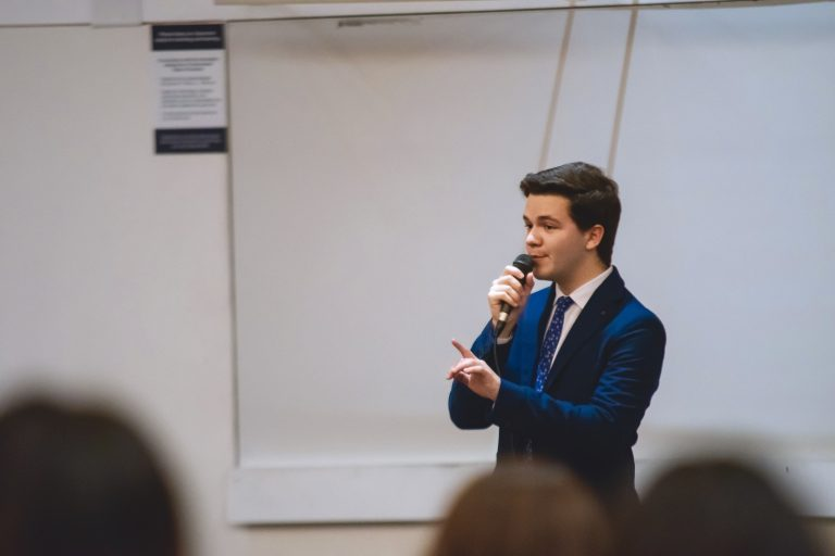 Alexander Mika '21 (CLAS) performs a stand-up comedy in a classroom.