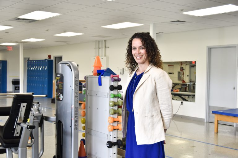 Smiling woman standing near gym equipment