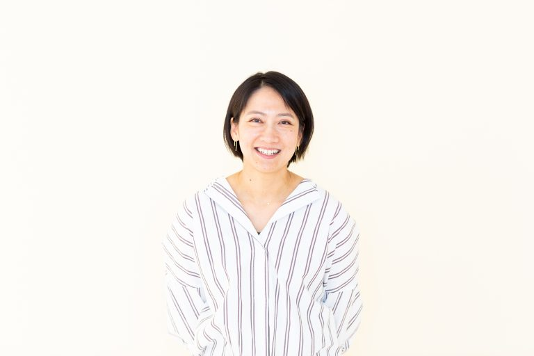 Smiling Asian woman stands in front of white background