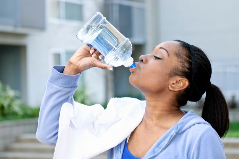 woman drinking water during exercise