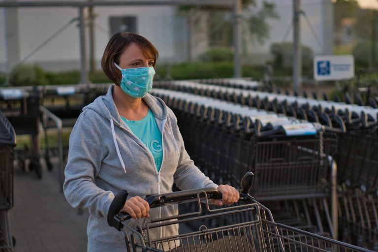 White middle-aged woman in a mask with a grocery cart