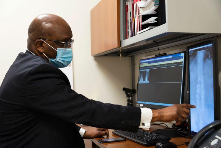 Dr. Hilary Onyiuke looking at spine image
