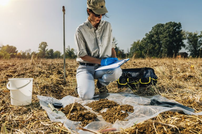 A scientist taking soil samples in a field. Field stations and marine laboratories are vital for scientists and the public, but the COVID-19 pandemic has jeopardized many of them.