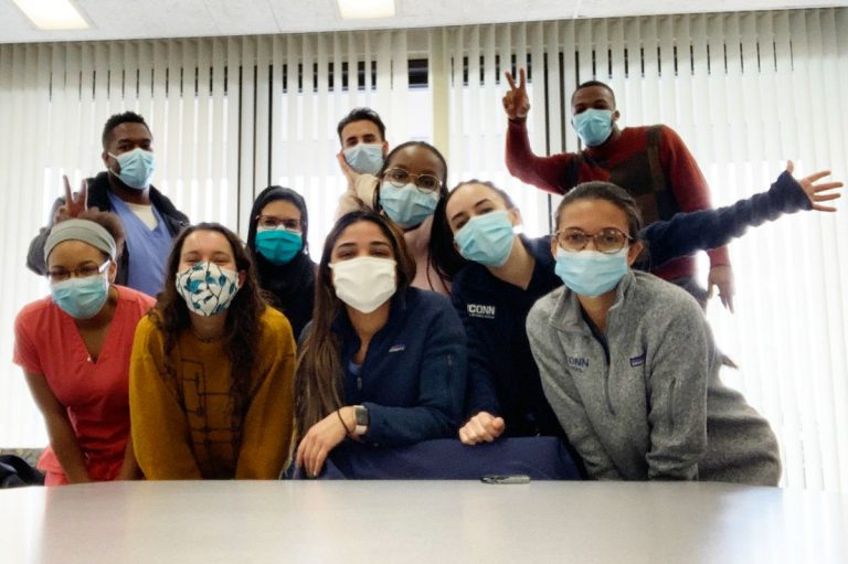 Group shot of dental students in masks behind a conference table