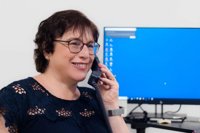 Social worker Sue Eisenberg speaking on an office phone