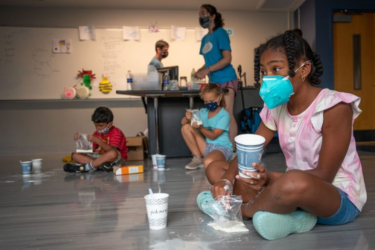 Nylah K., a student at BRAIN Camp, mixes corn starch and water to make oobleck during a camp activity.